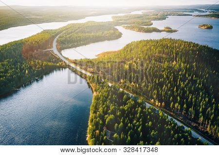 Aerial View Of Bridge Across Blue Lakes With Sun Light In Colorful Autumn Forest In Finland.
