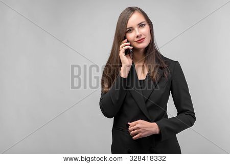 Young Beautiful Girl In Black Business Suit Talking On The Phone, White Background, Dark Straight Lo
