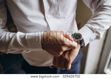 Close Up Of Mans Hand Fastening A Cuff Before Getting Married. Wedding Detail Man Puts Blue Cufflink