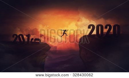 Surreal Scene, Man Jump Over A Chasm Obstacle Between 2019 And 2020 Years. Self Overcome, Starting A