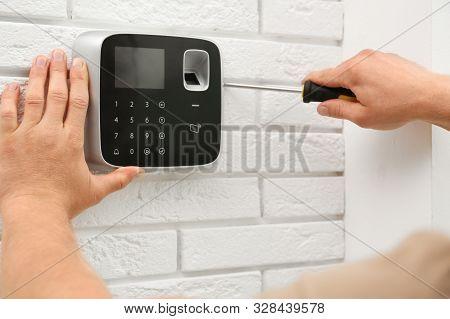 Male Technician Installing Security Alarm System Indoors, Closeup
