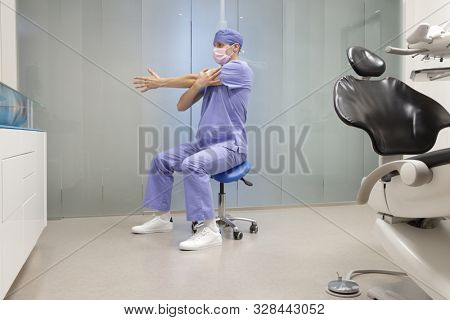Caucasian male, dentist in uniform  stretching arm in his office  - short break for exercise.