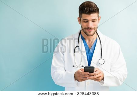 Hispanic Male Doctor Texting On Smartphone While Standing Against Plain Background