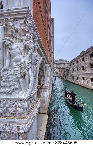 Venice, Italy - October 15, 2019: Gondola With Tourists Sails On Old Canal Under Medieval Bridge Of