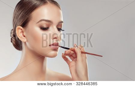 Makeup Artist Applies  Beige Gloss  Lipstick  . Beautiful Woman Face. Hand Of Make-up Master, Painti