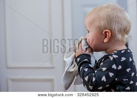 Little Girl Blows Her Nose Holding A White Handkerchief In Her Hands. The Child Blows His Nose. Seas