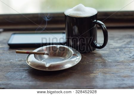 Coffee And Burning Cigarette In The Photo. Cup Of Cappuccino And Cigarette. Black Cup With Latte. Co