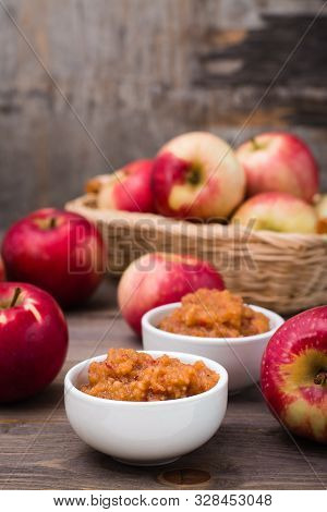 Fresh Applesauce In Bowls And Red Apples On A Wooden Table. Baby Food