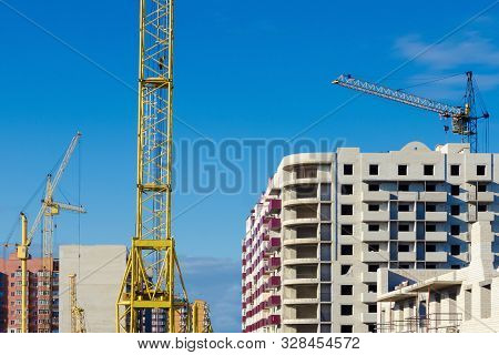 Construction Cranes On The Background Of Multi-apartment Buildings Under Construction. The Concept O