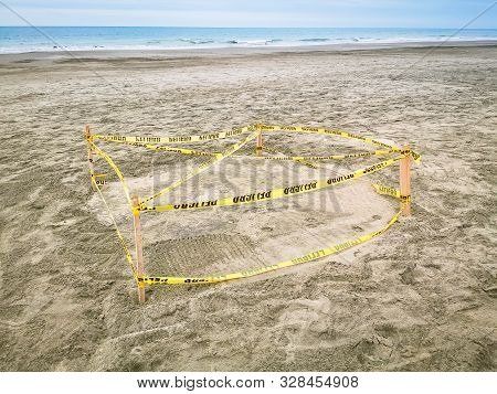 Protected Sea Turtle Nest. Barricaded Sea Turtle Nest With Yellow Tape And Ground Meshing On The Bea