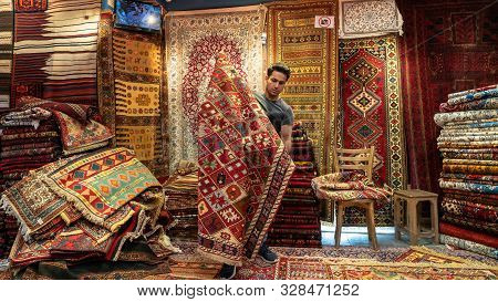 Isfihan, Iran - May 2019: Young Iranian Carpet Seller Presenting Persian Carpets To Tourists In A Ca