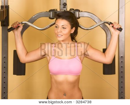 Female Performing Exercises On Weight-Lifting Training Machine