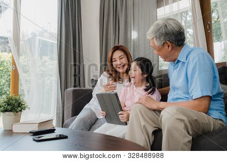 Asian Grandparents And Granddaughter Using Tablet At Home. Senior Chinese, Grandpa And Grandma Happy