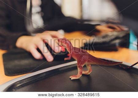 Shooting Tyrannosaurus T-rex Dinosaur Against The Background Of A Programmer At A Computer.