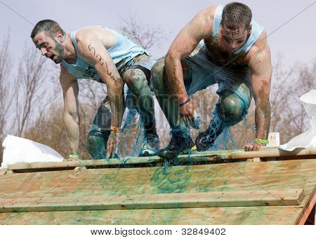 POCONO MANOR, PA - APR 28: Two men emerge from a tank filled with water and ice at Tough Mudder on April 28, 2012 in Pocono Manor, PA. The course is designed by British Special Forces.