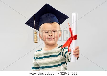 elementary school, preschool education and childhood concept - portrait of smiling little boy in mortar board with diploma over grey background