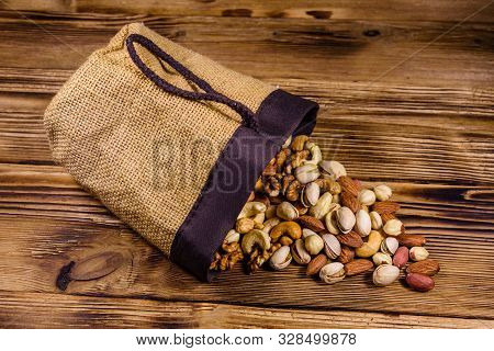 Various Nuts (almond, Cashew, Hazelnut, Pistachio, Walnut) Scattered From Bag On Wooden Table. Veget