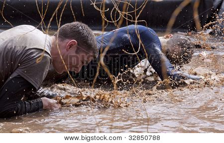 POCONO MANOR, PA - APR 28: Two men crawl through water under electrified wires at Tough Mudder event on April 28, 2012 in Pocono Manor, Pennsylvania. The course is designed by British Royal troops.