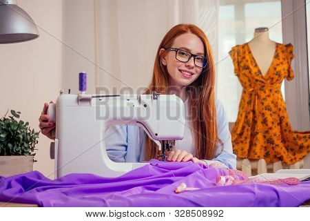 Red Haired Business Woman With Sewing Machine And Maniken In Studio Background. Tailor Creates A Col