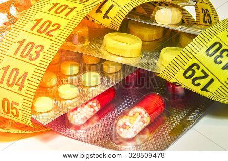 Pills With Measuring Tape, Represent The Diet Pill Industry. Diet Meds Concept