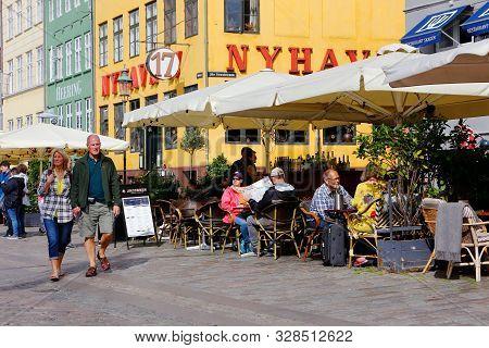 Copenhagen, Denmark - September 4, 2019: A Couple Are Walking In The Nyhavn District Alongside The R