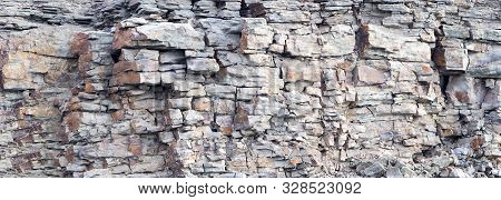 Rock Cliff Face Background. Dangerous Vertical Wall With Protruding Crumbling Layered Stone Blocks I