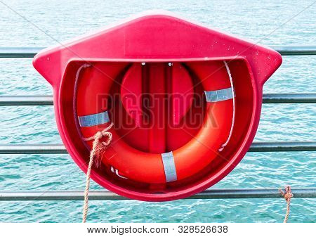 Red Life Preserver On Display On The Sea Dock.