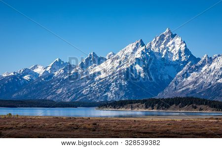 Snow Cover Mountain Peak Of Grand Teton Outstanding In Blue Sky Beside Jackson Lake And Willow Flats