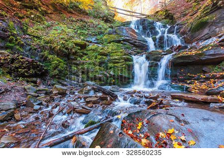 Waterfall Shypot Of Carpathian Mountains In Autumn. Powerful Stream Of Water. Brown Foliage On The R