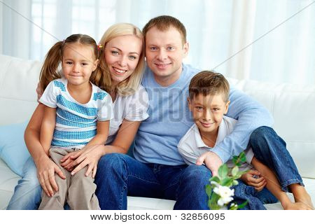 Portrait of happy Family mit zwei Kindern zu Hause zu sitzen