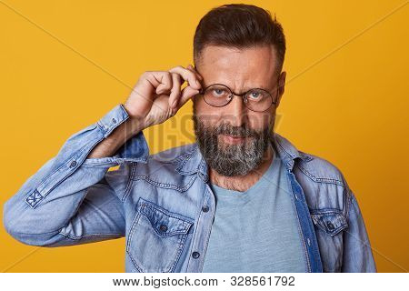 Photo Of Middleaged Bearded Man Keeps Hand On Rim Of Spectacles, Wearing Casual Clothes, Poses Again