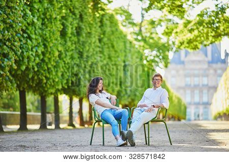 Happy Romantic Couple In Paris, Sitting On Traditional Green Metal Chairs In Tuileries Garden. Touri