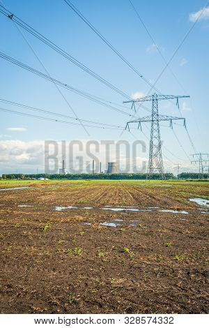 Converging High Voltage Lines And Power Pylons In A Dutch Rural Landscape. In The Background The Coo
