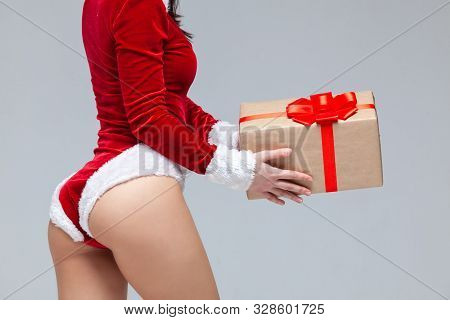 Christmas. Sports Fitness Girl In Red Sexy Santa Claus Costume Holding A Gift Box Tied With A Red Ri