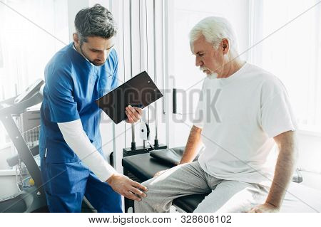 Physiotherapist Exam Patients Knee. Senior Patient With Knee Injury Visit His Physiotherapist
