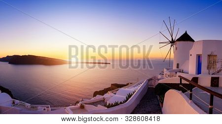 Sunset Over Santorini Island In Greece. Traditional Church, Apartments And Windmills In Oia Village