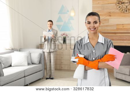 Portrait Of Young Chambermaid And Blurred Supervisor In Hotel Room. Space For Text