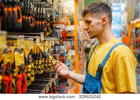 Male builder choosing pliers in hardware store