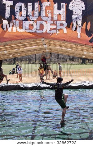 POCONO MANOR, PA - APR 29: A man falls into the water from the Funky Monkey obstacle at Tough Mudder on April 29, 2012 in Pocono Manor, Pennsylvania. The course is designed by British Royal troops.