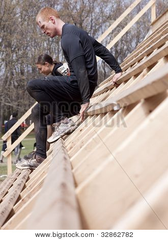POCONO MANOR, PA - APR 28: A man works his way down the steep incline of the Everest obstacle at Tough Mudder on April 28, 2012 in Pocono Manor, PA. The course is designed by British Special Forces.