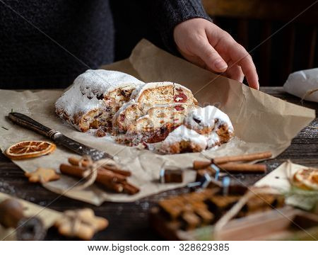 Sliced Homemade Christmas Dessert Stollen With Dried Berries And Nuts On Parchment In Woman Hand On