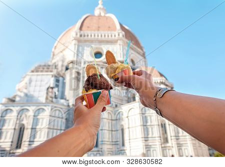 Women's Hands With Ice Cream Gelato On The Background Of The City Sight Cathedral Of Santa Maria Del
