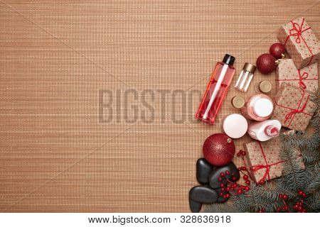 Spa still life with  toiletry, creams, gift boxes and Christmas ornaments on bamboo mat background. Top view with copy space. New Year and Christmas Healthy lifestyle, body care, Spa treatment poster