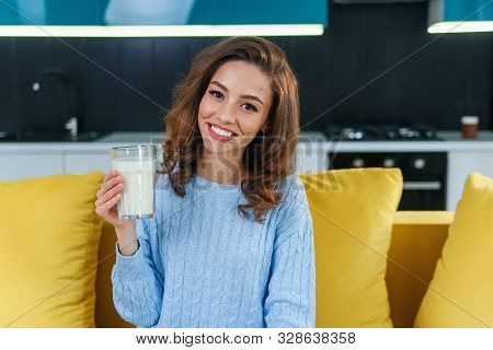 Attractive Woman Holds A Glass Of Fresh Milk And Drinks It In The Stylish Cozy Kitchen At The Mornin