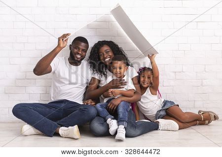 Mortgage For Young Families. Happy Black Parents And Their Two Kids Sitting Under Symbolic Roof Drea