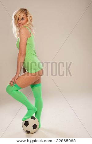 Beautiful blonde sexy athletic woman wearing green leggings and a short shirt exposing her buttocks posing with a football