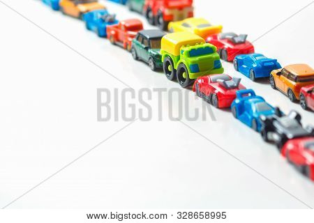 Plastic Multi-colored Toy Cars Are Lined Up On A White Background. Stereotypical Alignment Of Subjec