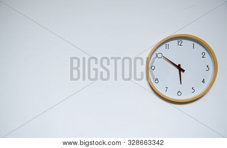 Portrait Of Yellow Circular Wall Clock On The White Wall Background. The Clock Has Time Of Round Abo