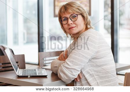 The Woman At Work Place In Caf , Office. Middle-aged Woman Doing Business In Behind A Laptop.