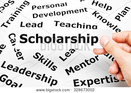 Hand Holding A Piece Of Paper With The Word Scholarship Printed On It Above Other Related Words In T